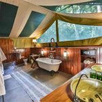 A spacious bathroom with bath and vanity basins at Governers Il Moran Camp