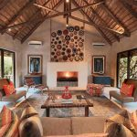 A lounge with couches and fireplace at Kapama South Camp