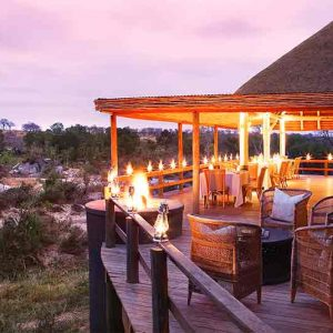 A wooden veranda with dinner tables overlooking the African bush