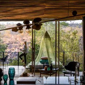 A person standing on a deck of a room at Singita Sweni