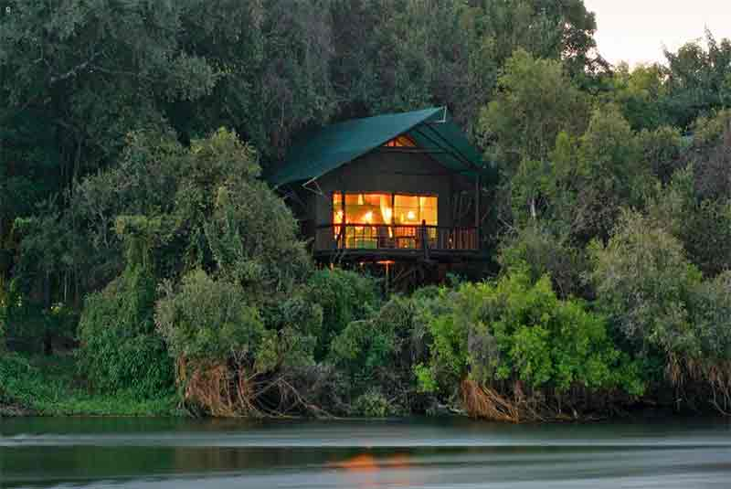 a tent on stilts on a river bank surrounded by trees