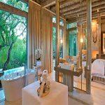 A bath and en suite bathroom next to a luxury rooom at Kapama Karula