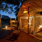 an open bedroom with double bed and table on a deck at night