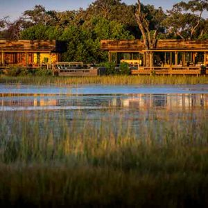A lodge set in amongst trees in front of a marsh
