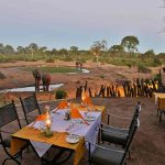 A dining table set up on a deck overlooking a water hole with Elephants drinking