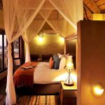 A room with a double bed and mosquito net