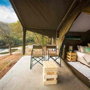An open tent with beds and views over a river at Iganyama