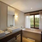 An en suite bathroom with views out to the bush