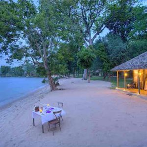 A chalet and table on a beach on Rubondo Island Camp