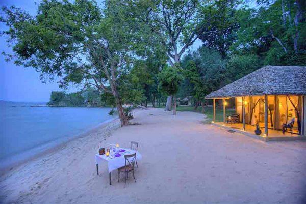 A chalet and table on a beach on Rubondo Island Camp