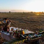 People sitting watching the sunset with drinks in Kafue national park