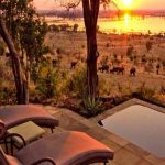 A small deck with sun loungers and a plunge pool with views of the sun setting over an open plain