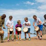 Several children with a guide at Little Kulala Lodge playing drums