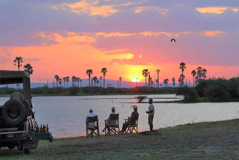People sitting at the edge of a lake watching the sunset