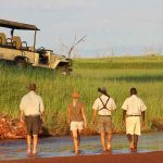 People walking through water towards a vehicle in Africa