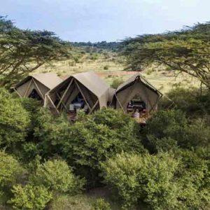 A safari tent in Kenya set amongst some trees'