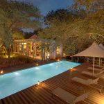 Swimming pool and deck with trees at Kapama Karula