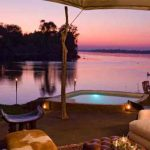 a private pool on a small deck overlooking a river at sunset