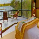 a tent with double bed and small deck overlooking a river