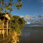 a wooden chalet on the banks of a river