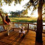 Couple standing on wooden deck overlooking the Okavango Delta at Gunns Camp
