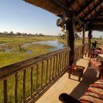 Wooden deck with lounge area overlooking the Okavango floodplain at Gunns Camp