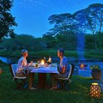 Guests dining at night with a fire close by on the river banks