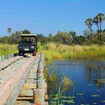 A vehicle driving over a wooden bridge in the Okavango Delta