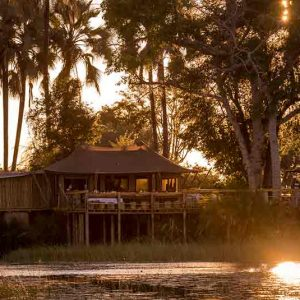 A lodge under trees ona river bank at twilight