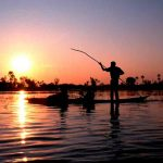 a man on a small canoe in the middle of the river fishing at sunset