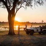 A vehicle with people in front of a waterhole at sunset