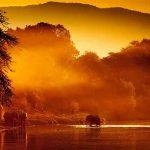 An elephant walking out of the zambezi river at sunset