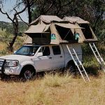 A vehicle standing in the bush with two open roof top tents