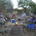 A group of people sitting in a circle in the African bush