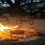A burning fire surrounded by chairs in the bush