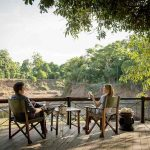Two people sitting on a deck overlooking the Mara River at Governers Camp
