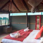 bedroom interior with double bed looking out to the african bush