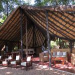 a thatched roof with chairs and couches underneath