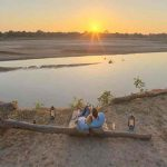 two people lying on a river bank watching the sunset over the river