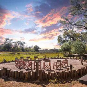 A circular fire area with chairs and views of the bush