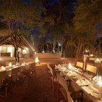 Tables and chairs laid for dinner with lights at night