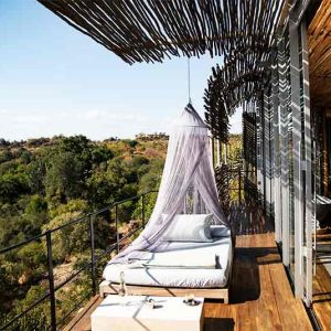 A room and outside deck with mattress and mosquito net overlooking a river