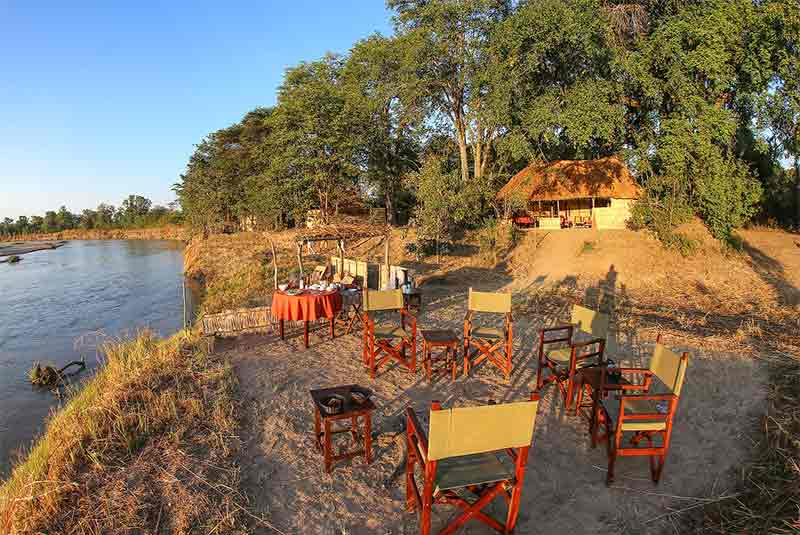 chairs on sand on a river bank
