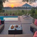 a deck with swimming pool and umbrella with teh sun setting in the distance