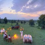 People sitting at a table on a grass hillside in kenya