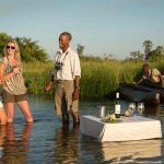A guide and guests enjoy drinks while standing in water