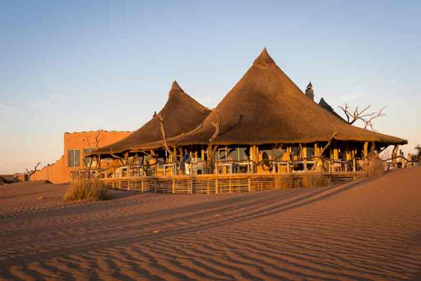 A thatch roof lodge set amongst the dunes of Namibia