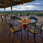 A deck with tables and chairs at Doro Nawas for a meal