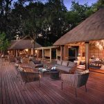 A large wooden deck with chairs and tables at &Beyond Nxabega