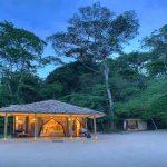 A chalet at Rubondo Island Camp lit up at dusk
